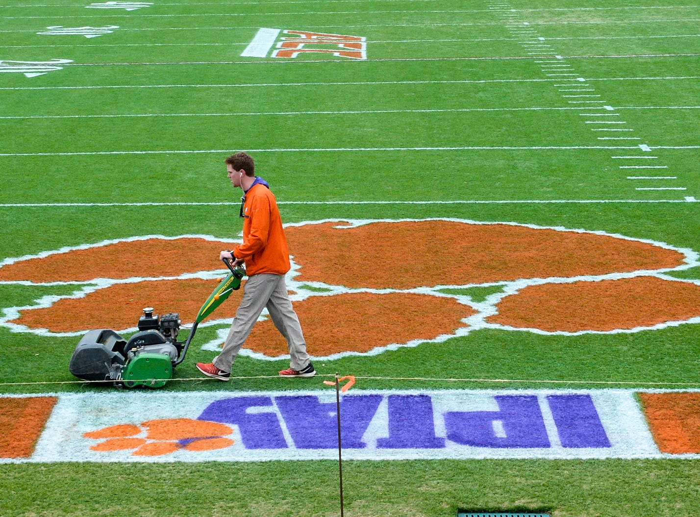 Philip Rhodes, left, Clemson University Athletic Grounds, coworkers Marshall Wagner, and Dan McKinney, run grass trimming machines over the field seven hours before kickoff in Memorial Stadium, before the South Carolina at Clemson football game in Clemson on Saturday, November 24, 2018.