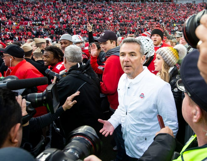 Ohio State coach Urban Meyer searches the crowd as fans rush the field after the Buckeyes' resounding 62-39 win over Michigan.