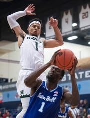 Hawaii guard Drew Buggs, top, leaps to defend Seton Hall forward Michael Nzei from shooting during the second half of an NCAA college basketball game at the Wooden Legacy tournament.