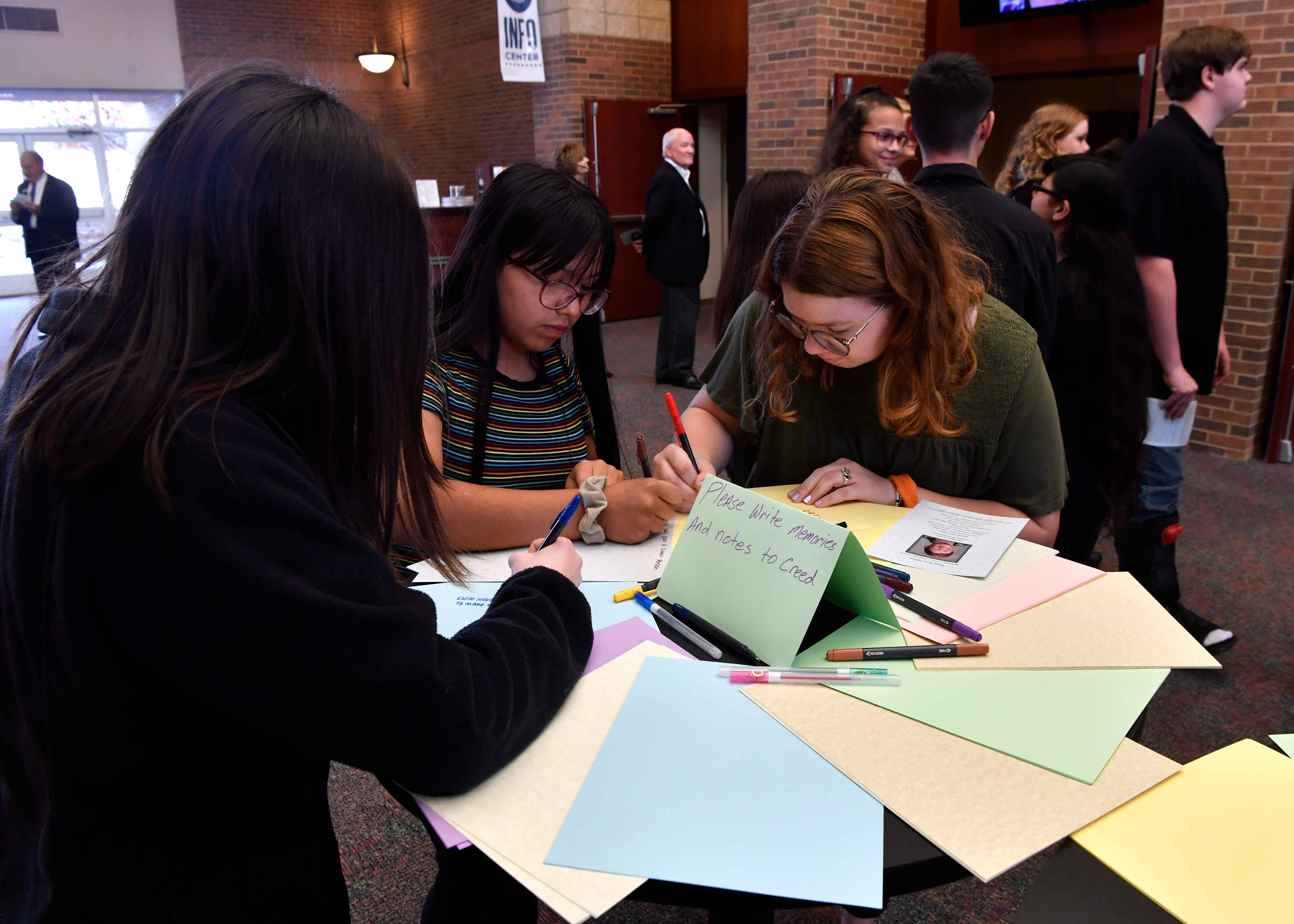 Avery Kerr, (left), Yasmine Hernandez and Emma Skaggs write notes of condolence before the memorial service of Creed Ryan Parrish Saturday.