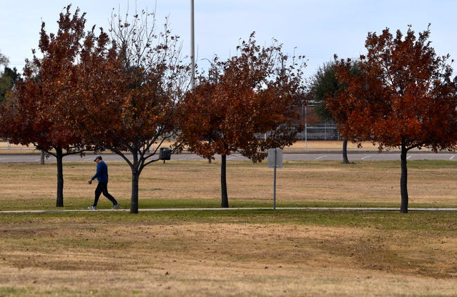 A pedestrian strolls down the walking path at Nelson Park Saturday.