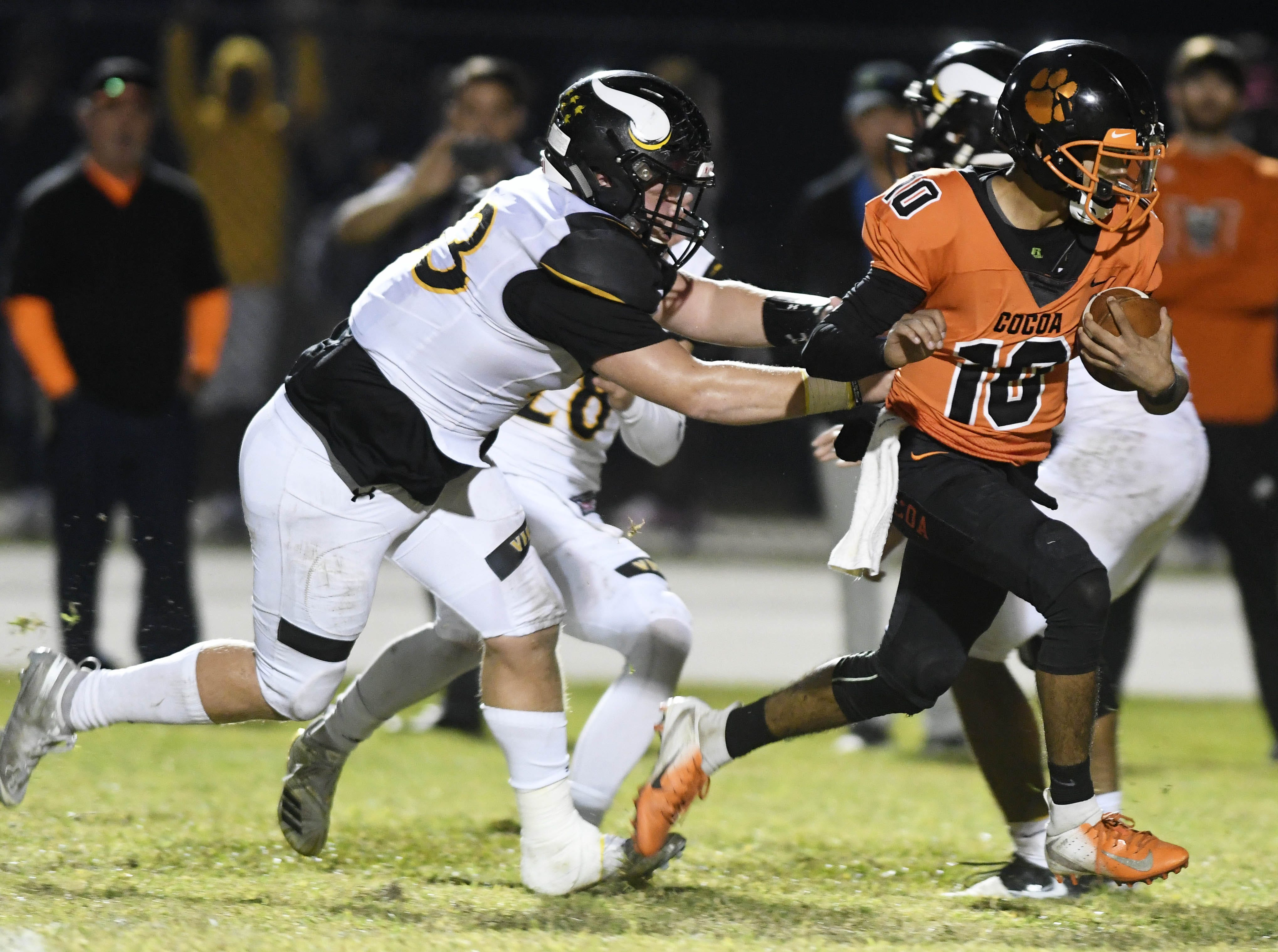 Cocoa QB Diego Arroyo is pursued by Brandon Peck (33) of Bishop Verot during Friday's game at Blake Stadium.