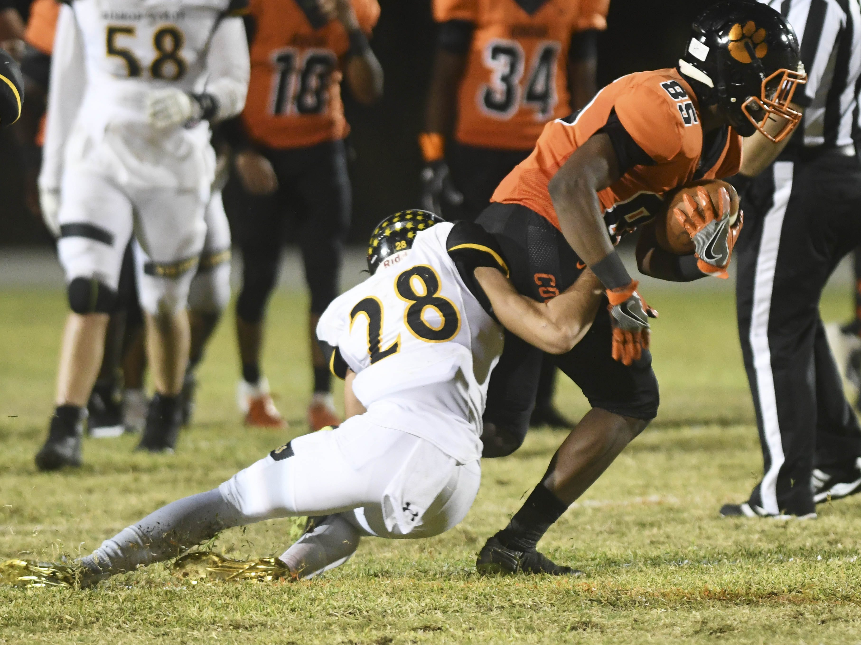 Demarquez Henley of Cocoa is dragged down by Derrick Erickson of Bishop Verot after making a first down catch during Friday's game.