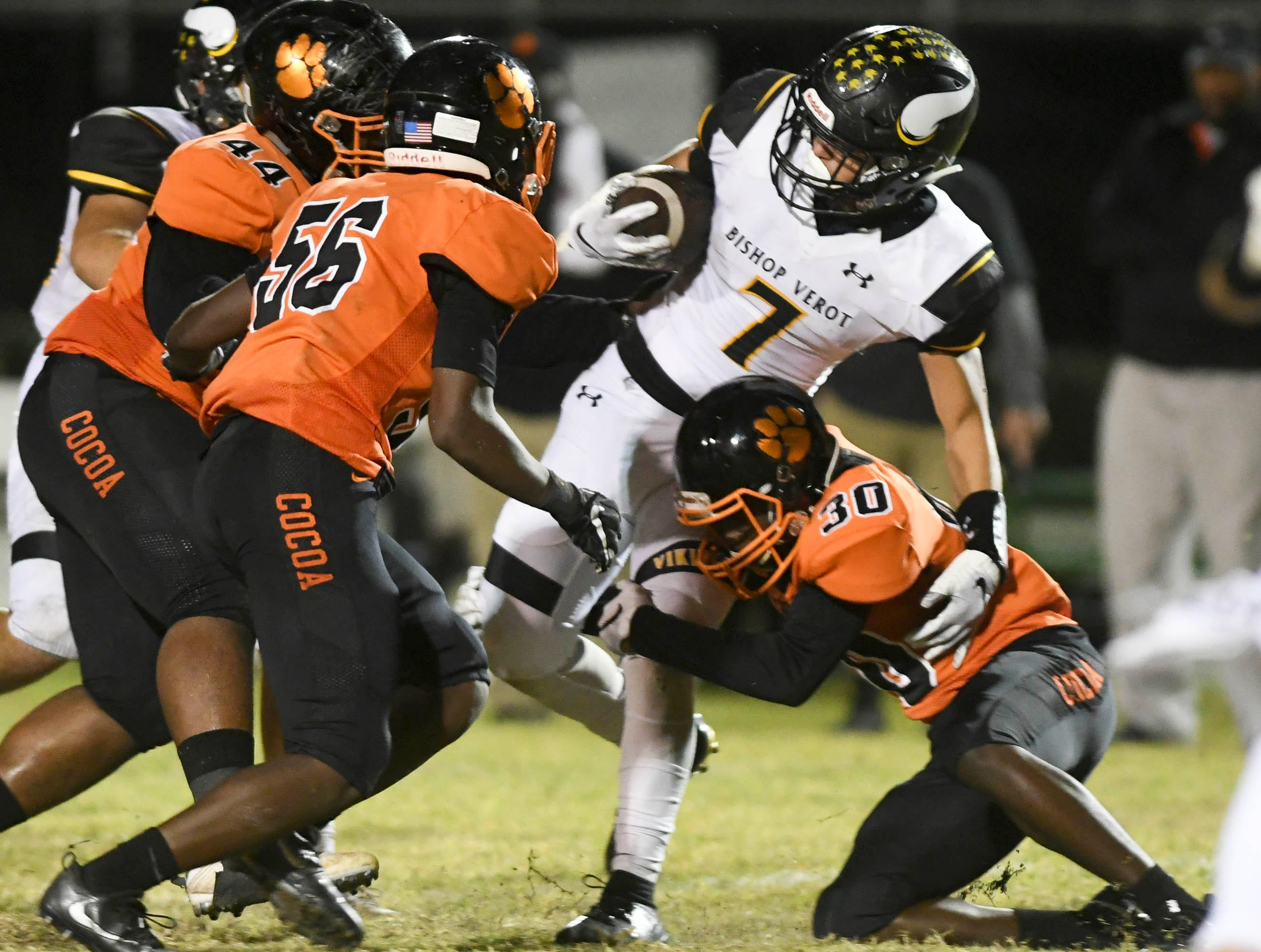 Dominic Febles of Bishop Verot (7) is tackled by Dajavon White (44) AJ Williams (56) and Ja'Quez Hicks of Cocoa during Friday's regional final at Blake Stadium.