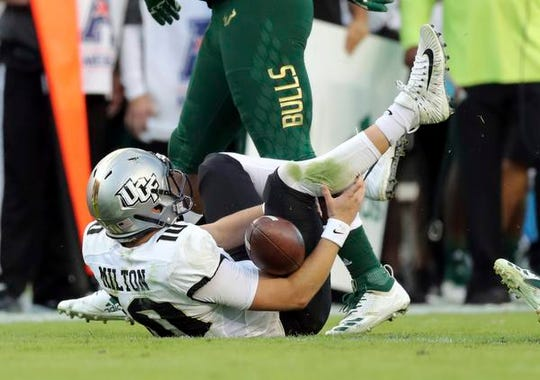Central Florida quarterback McKenzie Milton goes down with an apparent knee injury after being tackled during the first half of an NCAA college football game against South Florida on Friday, Nov. 23, 2018, in Tampa, Fla. (