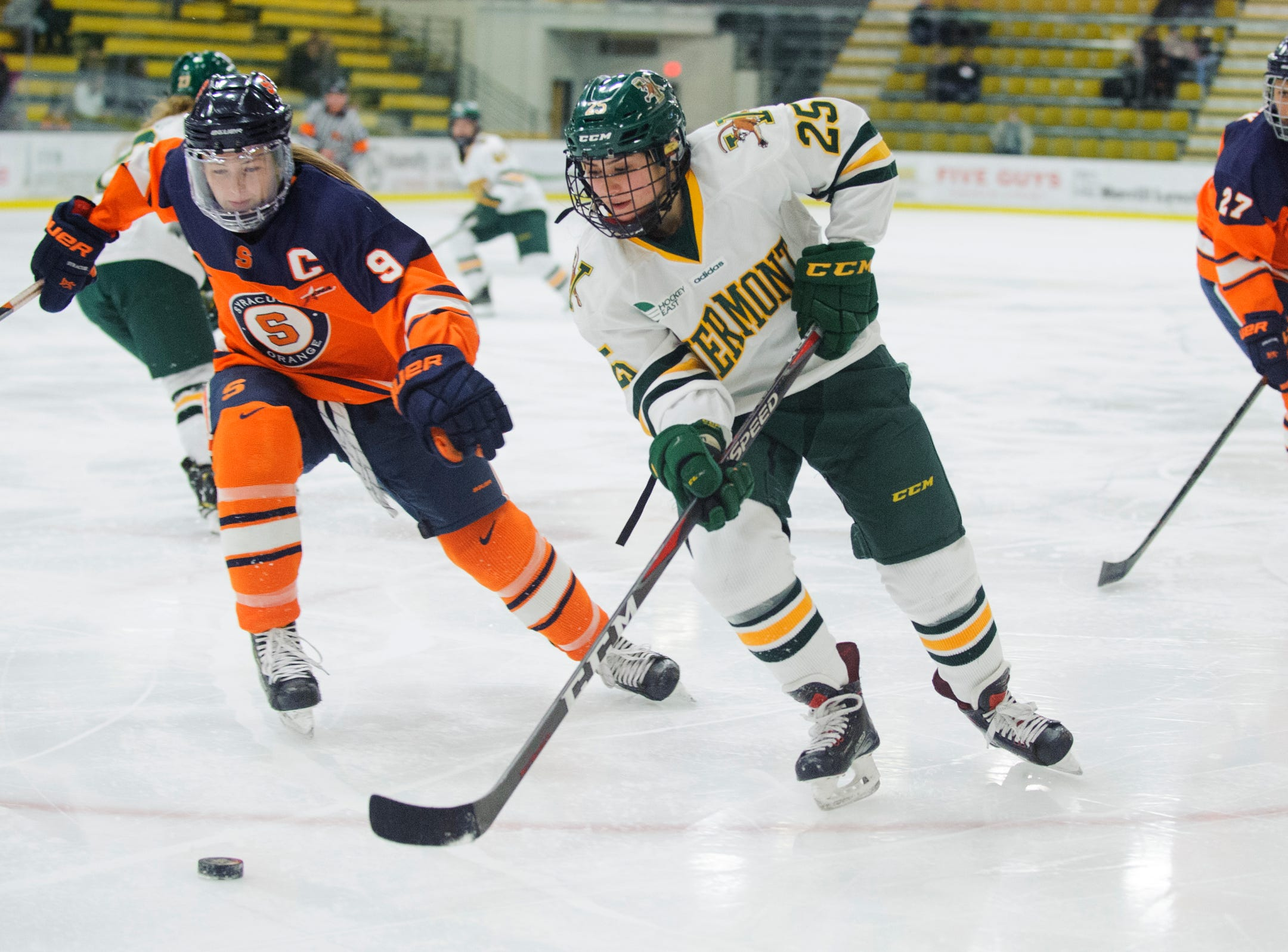 Vermont's Alyssa Holmes (25) skates past Syracuse's Allie Monroe (9) with the puck during the women's hockey game between the Syracuse Orange and the Vermont Catamounts at Gutterson Field House on Friday night November 23, 2018 in Burlington.