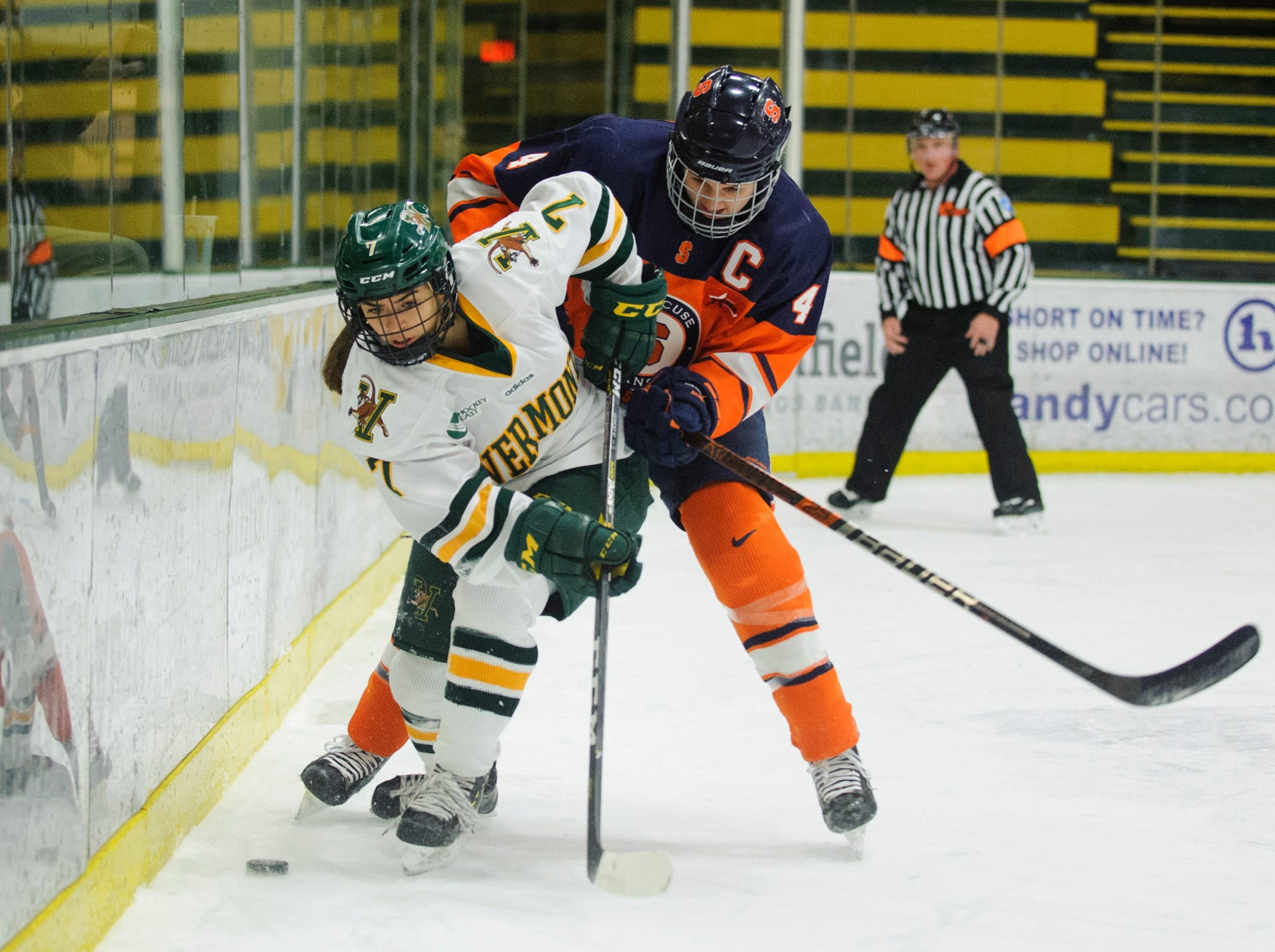 Vermont's Lristina Shanahan (7) battles for the puck with Syracuse's Lindsay Eastwood (4) during the women's hockey game between the Syracuse Orange and the Vermont Catamounts at Gutterson Field House on Friday night November 23, 2018 in Burlington.