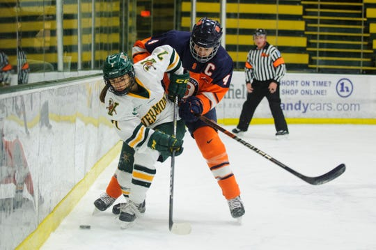 Vermont's Kristina Shanahan (7) battles for the puck with Syracuse's Lindsay Eastwood (4) during the women's hockey game between the Syracuse Orange and the Vermont Catamounts at Gutterson Fieldhouse in November.