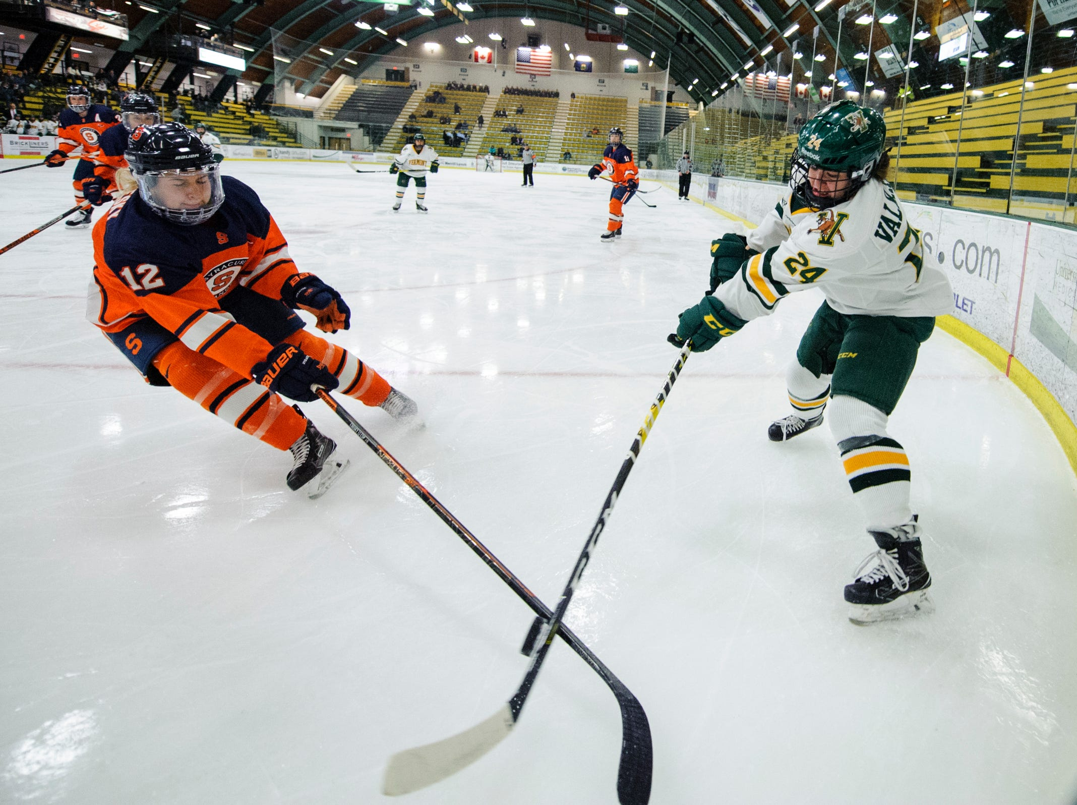 Vermont's Saana Valkama (24) battles for the puck with Syracuse' Kristen Siemachesky (12) during the women's hockey game between the Syracuse Orange and the Vermont Catamounts at Gutterson Field House on Friday night November 23, 2018 in Burlington.