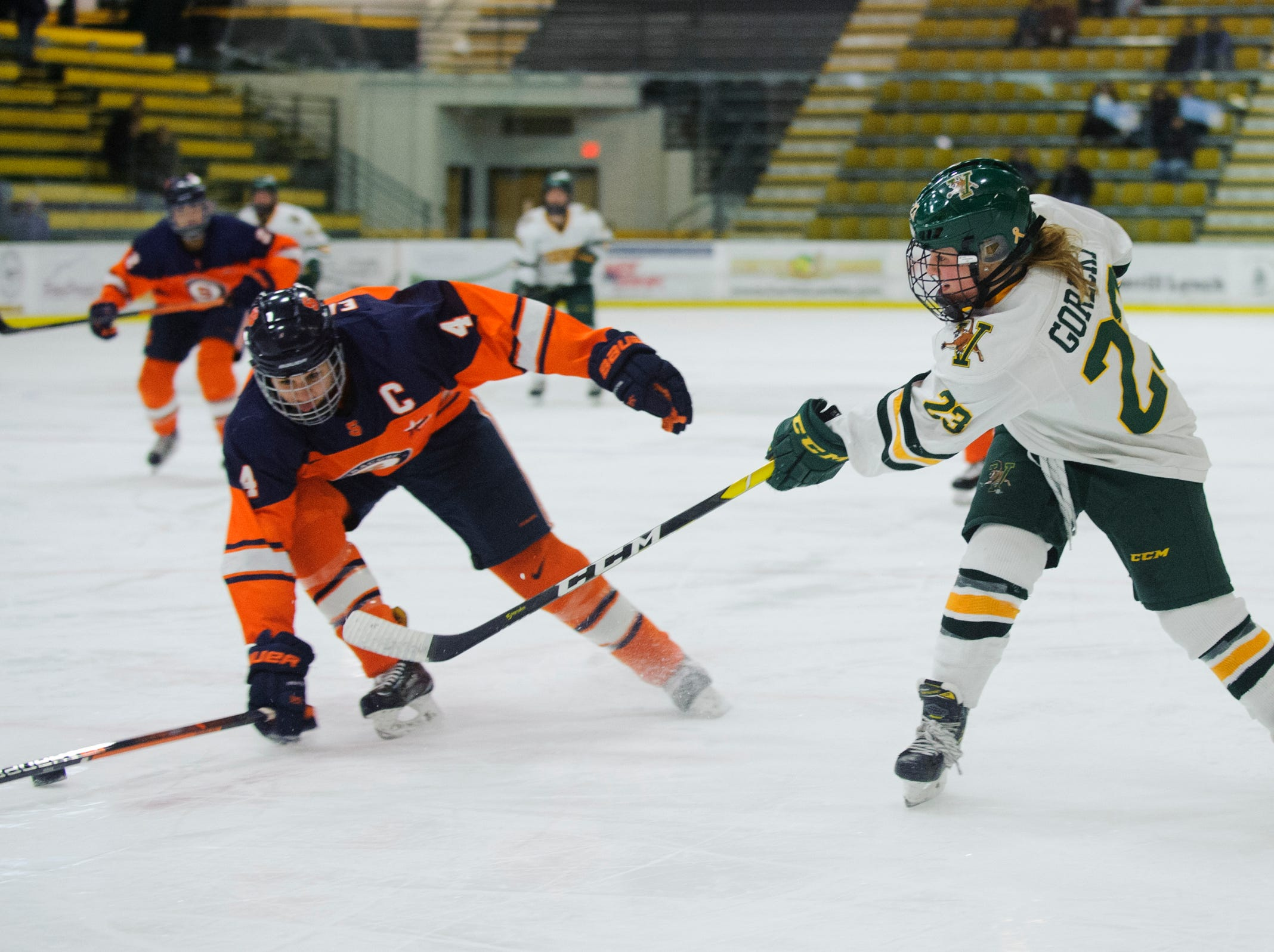 Vermont's Alyssa Gorecki (23) shoots the puck past Syracuse's Lindsay Eastwood (4) during the women's hockey game between the Syracuse Orange and the Vermont Catamounts at Gutterson Field House on Friday night November 23, 2018 in Burlington.