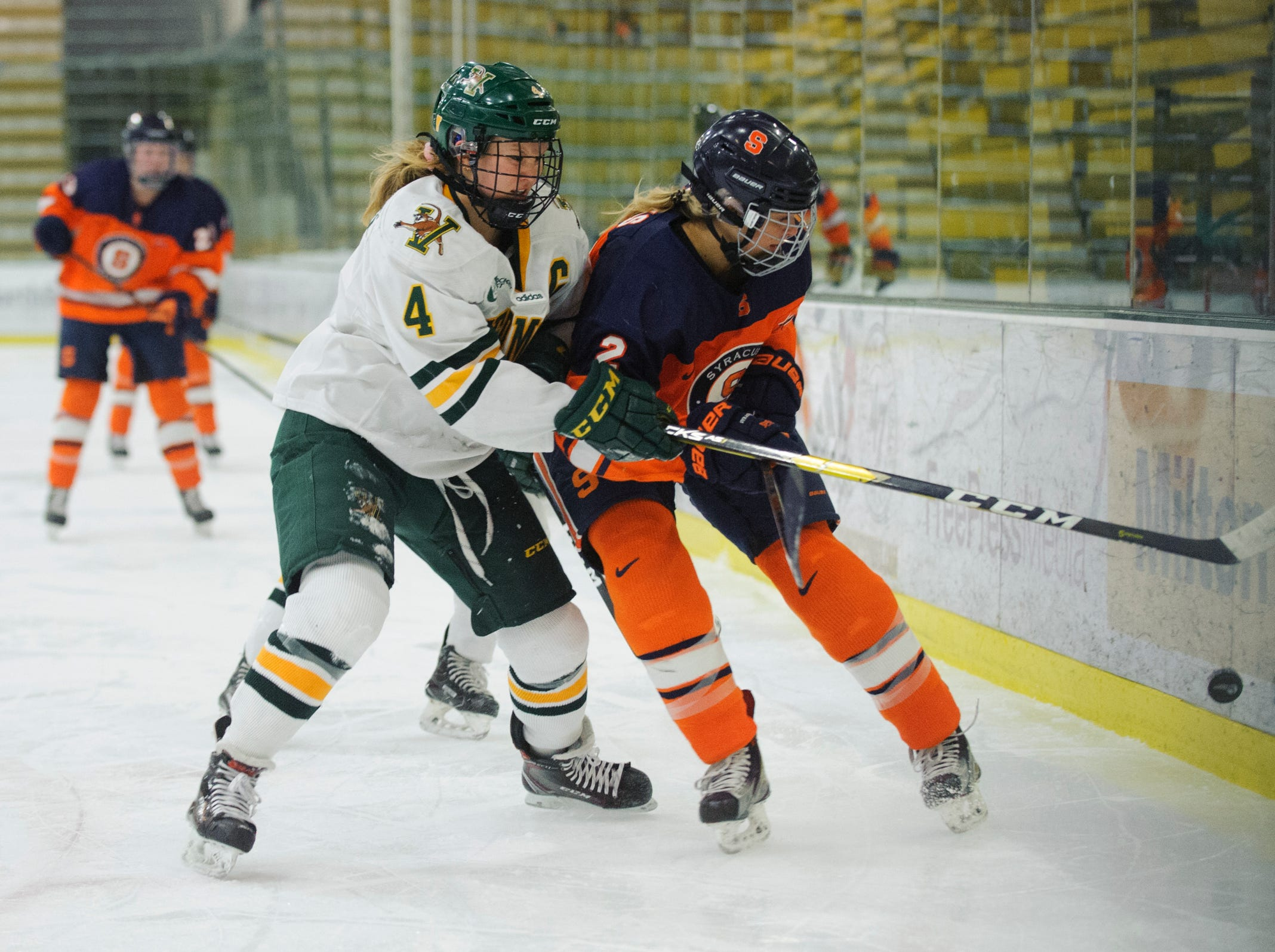 Vermont's Sammy Kolwart (4) battles for the puck with Syracuse's Logan Hicks (2) during the women's hockey game between the Syracuse Orange and the Vermont Catamounts at Gutterson Field House on Friday night November 23, 2018 in Burlington.