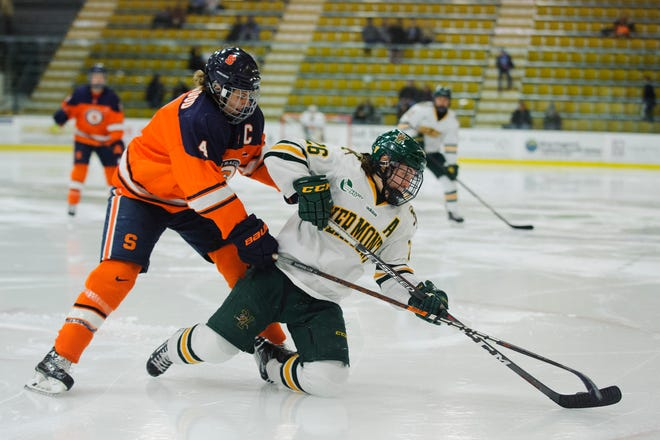Eve-Audrey Picard (26) and Syracuse's Linsday Eastwood (4) battle for the puck during the women's hockey game between the Syracuse Orange and the Vermont Catamounts at Gutterson Field House on Friday night November 23, 2018 in Burlington.