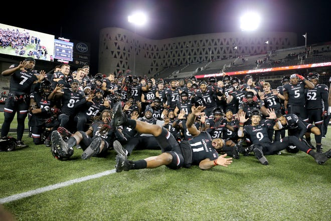 The Cincinnati Bearcats football team pose for a photo after earning their 10th win of the season, a 56-6 win against the East Carolina Pirates, Friday, Nov. 23, 2018, at Nippert Stadium in Cincinnati.