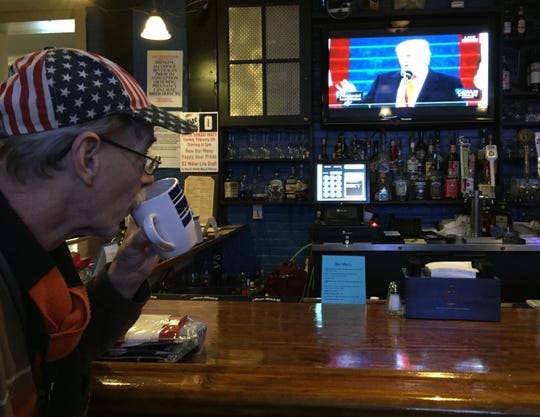 Presidents Inn co-owner Michael Carver sips a coffee while watching President Donald Trump's inauguration inside the Boone County restaurant and bar, Jan. 20, 2017.