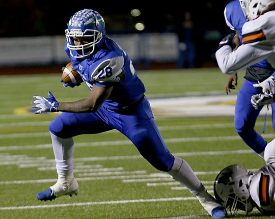 Winton Woods running back Miyan Williams escapes a Massillon Washington defender during their Division II state semifinal at Gahanna Friday, Nov. 23, 2018.