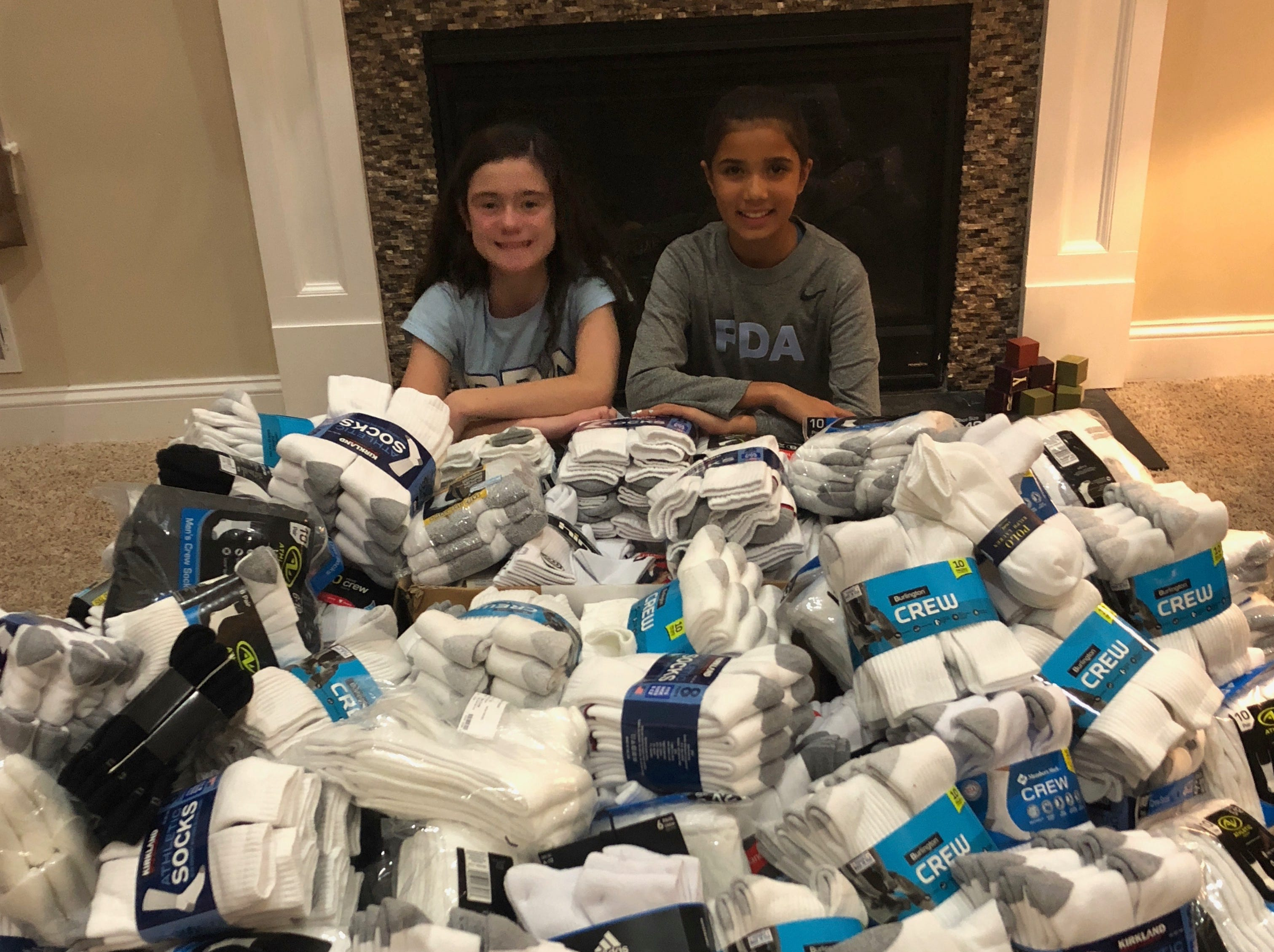 Maddie O'Neill and Kaya Singh with a large pile of socks collected through the generosity of the PDA community.