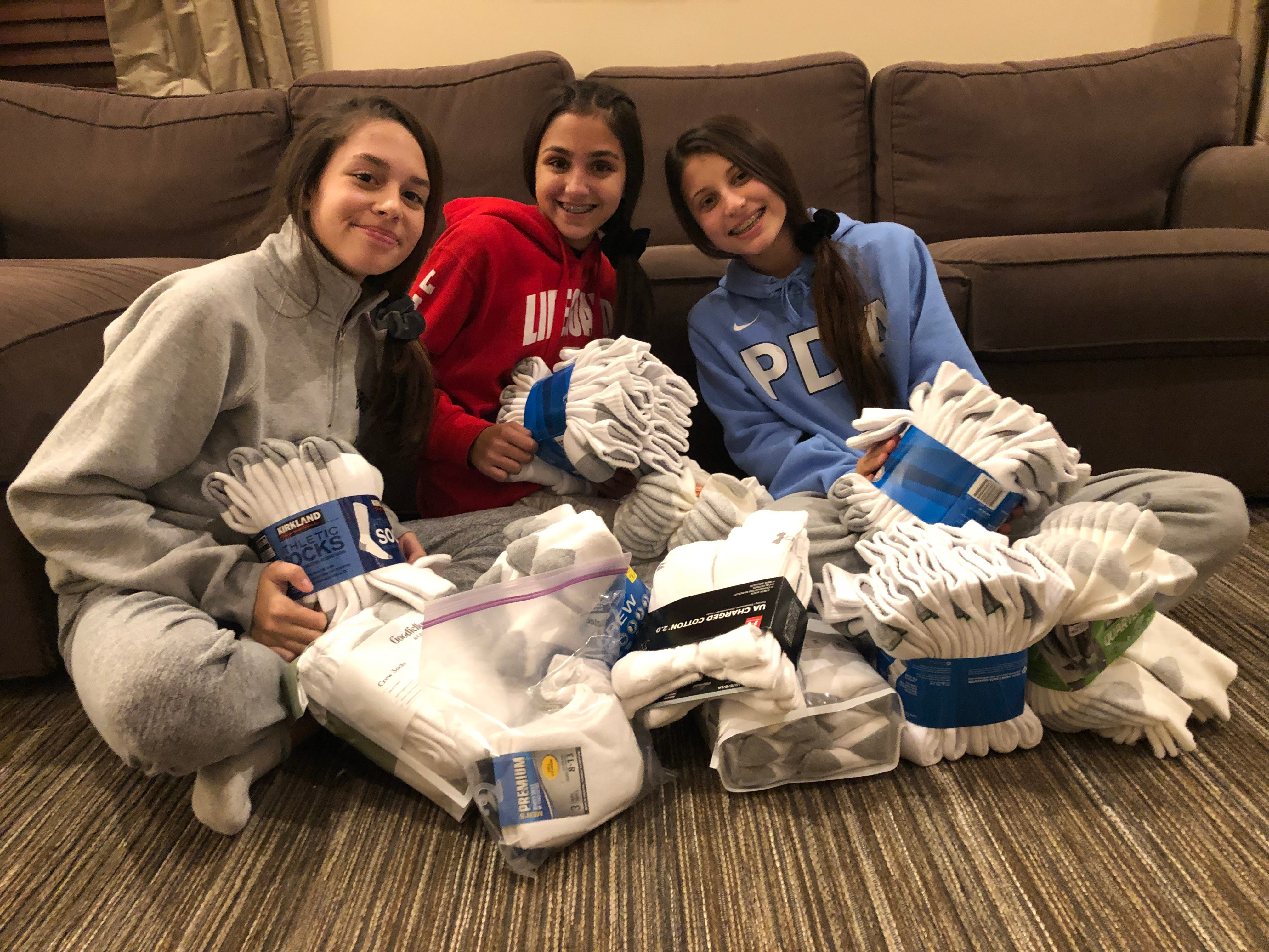 Grace Miraglia, Gia D'Ambrosia and Angelina Lomanto collect socks from neighbors.