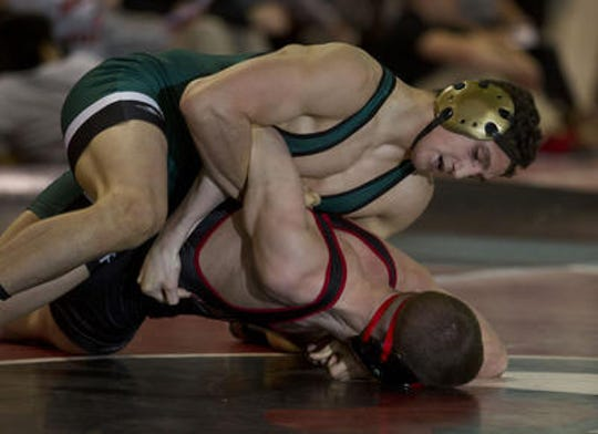 As a high school senior, Ray Jazikoff, top, wrestles Jackson Memorial's Tanner Kelly.