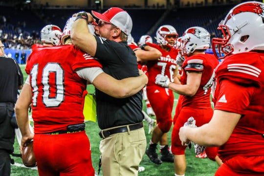 Chippewa Valley Head Coach Scott Merchant embraces Quarterback Tommy Schuster after defeating Clarkston in the Division 1 MHSAA State Championship at Ford Field in Detroit on Saturday, Nov. 24, 2018.