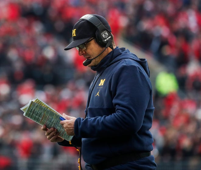 Michigan head coach Jim Harbaugh looks down at his notes during a timeout in the second half against Ohio State at Ohio Stadium in Columbus, Ohio, Saturday, Nov. 24, 2018.