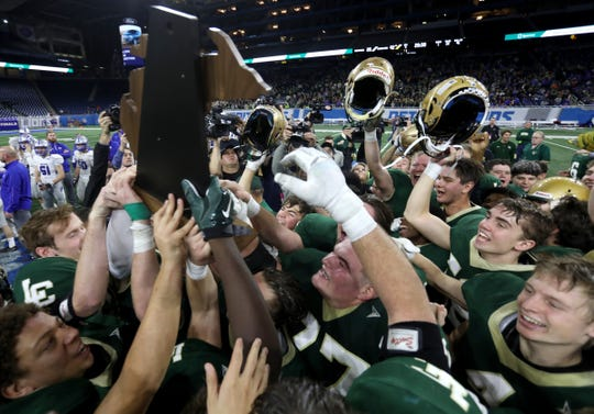 Jackson Lumen Christi players celebrate with the trophy after beating Montague 42-28 to win the division 6 MHSAA football final at Ford Field in Detroit on Friday November 23, 2018.