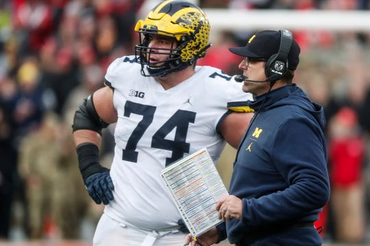 Michigan head coach Jim Harbaugh talks to offensive line Ben Bredeson at a timeout during the second half against Ohio State at Ohio Stadium in Columbus, Ohio, Saturday, Nov. 24, 2018.