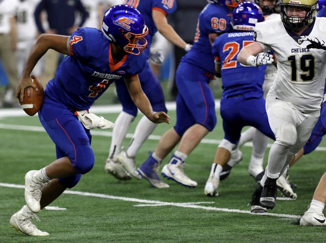Edwardsburg quarterback Tre' Harvey (4) hides the football behind him as he scrambles out of the pocket for a run during first-half action between Edwardsburg and Chelsea in division 4 MHSAA football final at Ford Field in Detroit on Friday November 23, 2018.