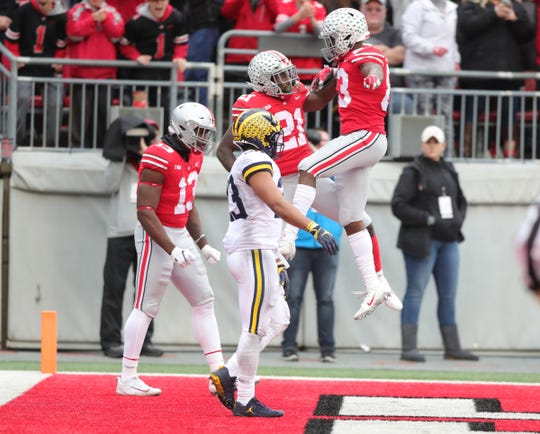 Michigan defensive back Tyree Kinnell walks by as Ohio State running back Paris Campbell (21) celebrates his touchdown during the second half Saturday, Nov. 24, 2018 at Ohio Stadium in Columbus, Ohio.