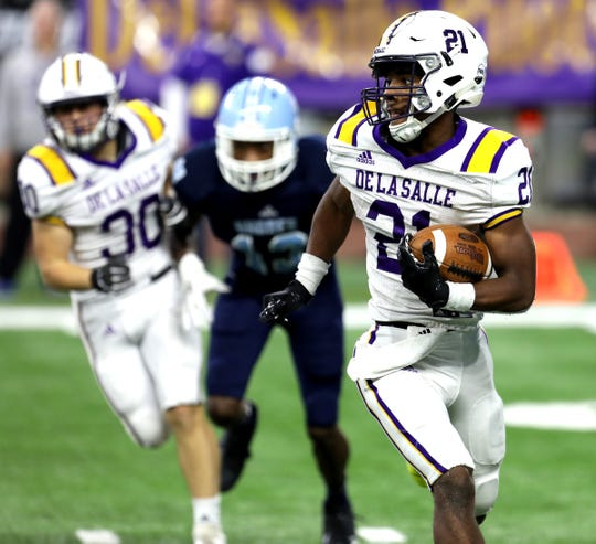 Warren De La Salle #21 Joshua DeBerry runs across the field looking for an open hole during first half action in the division 2 MHSAA football finals between Warren De La Salle and Muskegon Mona Shores at Ford Field in Detroit on Friday November 23, 2018.