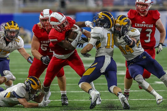 Chippewa Valley Ja'Von Kimpson runs for yards against Clarkston Josh Luther (18) during the first half of the Division 1 MHSAA State Championship at Ford Field in Detroit on Saturday, Nov. 24, 2018.