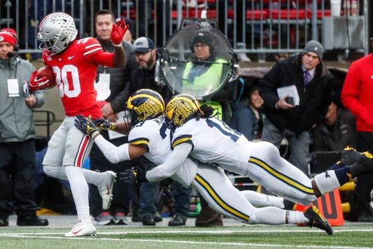 Michigan linebacker Devin Bush (10) and defensive line Rashan Gray (3) try to stop Ohio State running back Demario McCall (30) during the first half at Ohio Stadium in Columbus, Ohio, Saturday, Nov. 24, 2018.