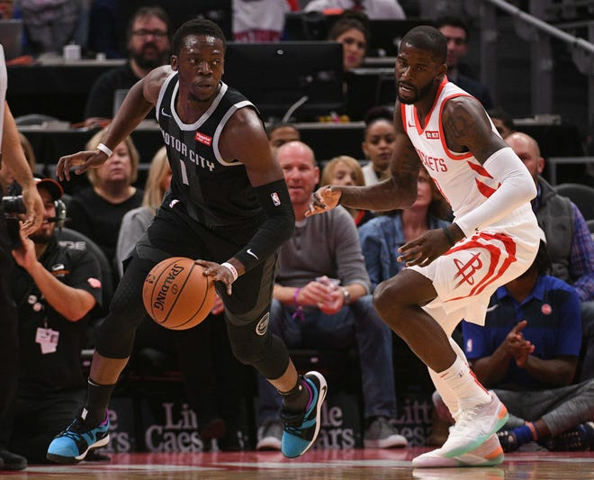 Pistons guard Reggie Jackson brings the ball up court as Rockets forward James Ennis III defends during the first quarter on Friday, Nov. 23, 2018, at Little Caesars Arena.