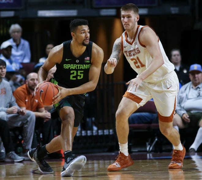 Michigan State's Kenny Goins moves the ball around Texas' Dylan Osetkowski during the first half on Friday, Nov. 23, 2018, in Las Vegas.