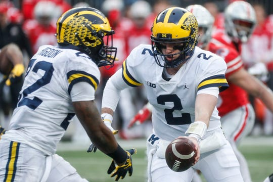 Shea Patterson hands to running back Karan Higdon during the first half against Ohio State.