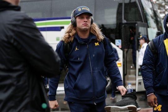 Michigan defensive line Chase Winovich walks off the bus as the team arrive at Ohio Stadium in Columbus, Ohio before the OSU game, Saturday, Nov. 24, 2018.