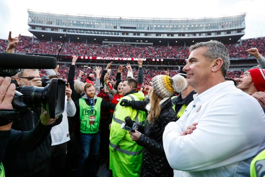 Ohio State head coach Urban Meyer smiles as he waits for his family on the field, after the 62-39 win over Michigan at Ohio Stadium in Columbus, Ohio, Saturday, Nov. 24, 2018.