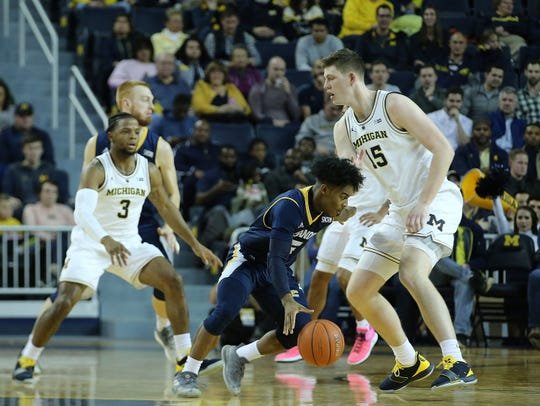 Chattanooga's Donovann Toatley drives the ball around Michigan's Jon Teske during the first half of U-M's 83-55 win on Friday, Nov. 23, 2018, at Crisler Center.