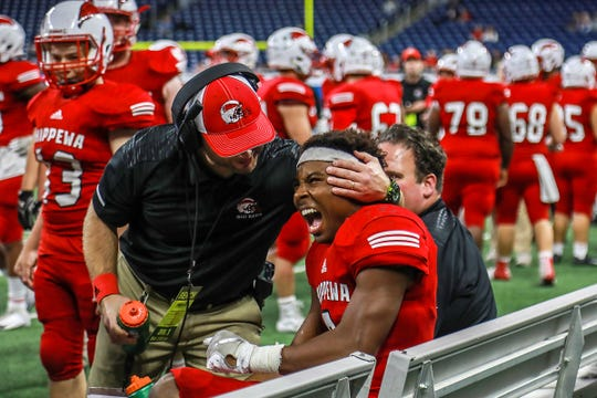 Chippewa Valley head coach Scott Merchant celebrates with David Ellis after he scored a touchdown before the half against Clarkston during the Division 1 MHSAA state championship at Ford Field in Detroit on Saturday, Nov. 24, 2018.