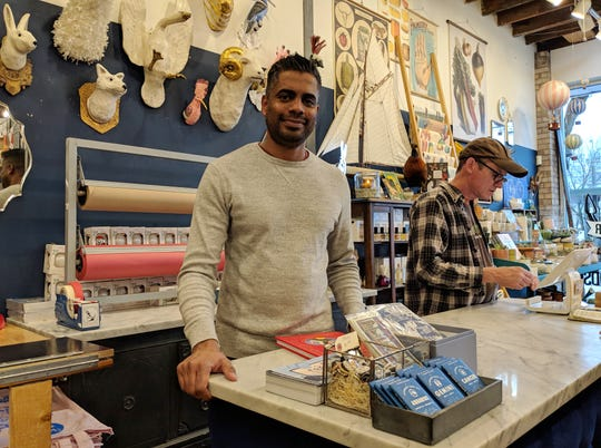 Rail & Anchor Owner Mathew Abraham (left) stands behind the store's counter. He says customers are greeted with a smile and a cup of tea.