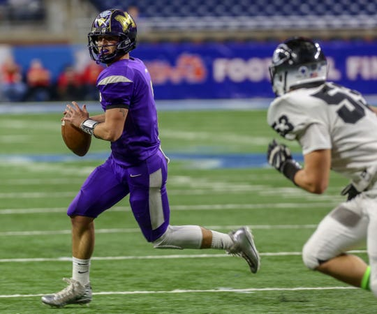 Madison Heights Quarterback Austin Brown runs away from the New Lothrop Chandler Saunders, during the Division 7 MHSAA State Championships at Ford Field in Detroit on Saturday, Nov. 24, 2018.