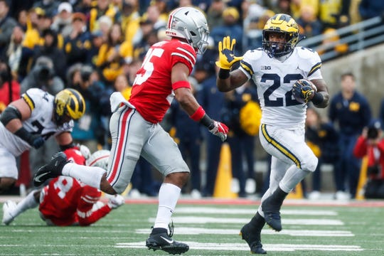 Michigan running back Karan Higdon (22) runs against Ohio State safety Brendon White (25) during the second half at Ohio Stadium in Columbus, Ohio, Saturday, Nov. 24, 2018.