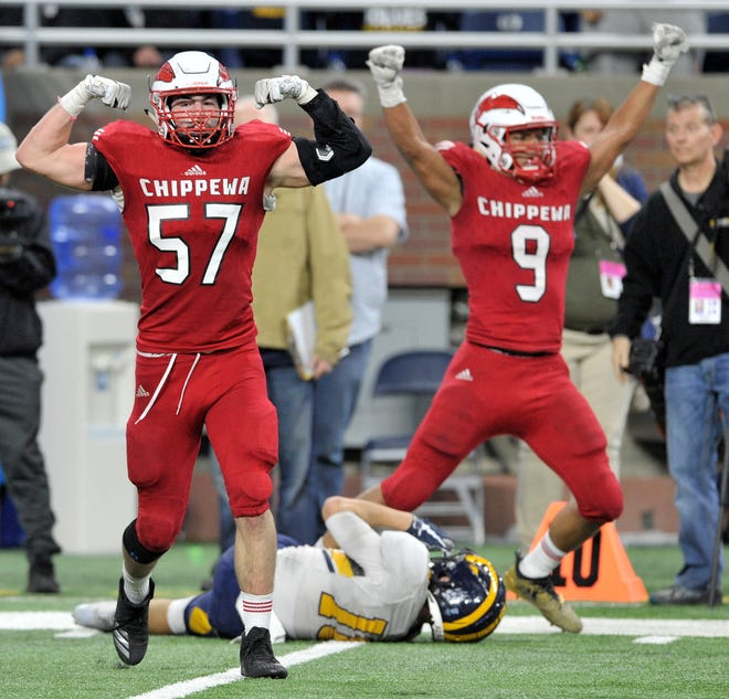 Chippewa Valley defensive lineman Michael Garwood (57) flexes after stopping Clarkston's Josh Luther from scoring a two-point conversion  as teammate Courtney McGarity (9) also celebrates.
