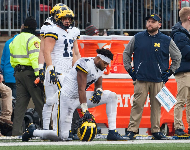 Michigan running back Tru Wilson (13) and wide receiver Nico Collins look disappointed on the sideline after Ohio State's Parris Campbell scored on a 78-yard touchdown run in make it 48-25 in the fourth quarter.