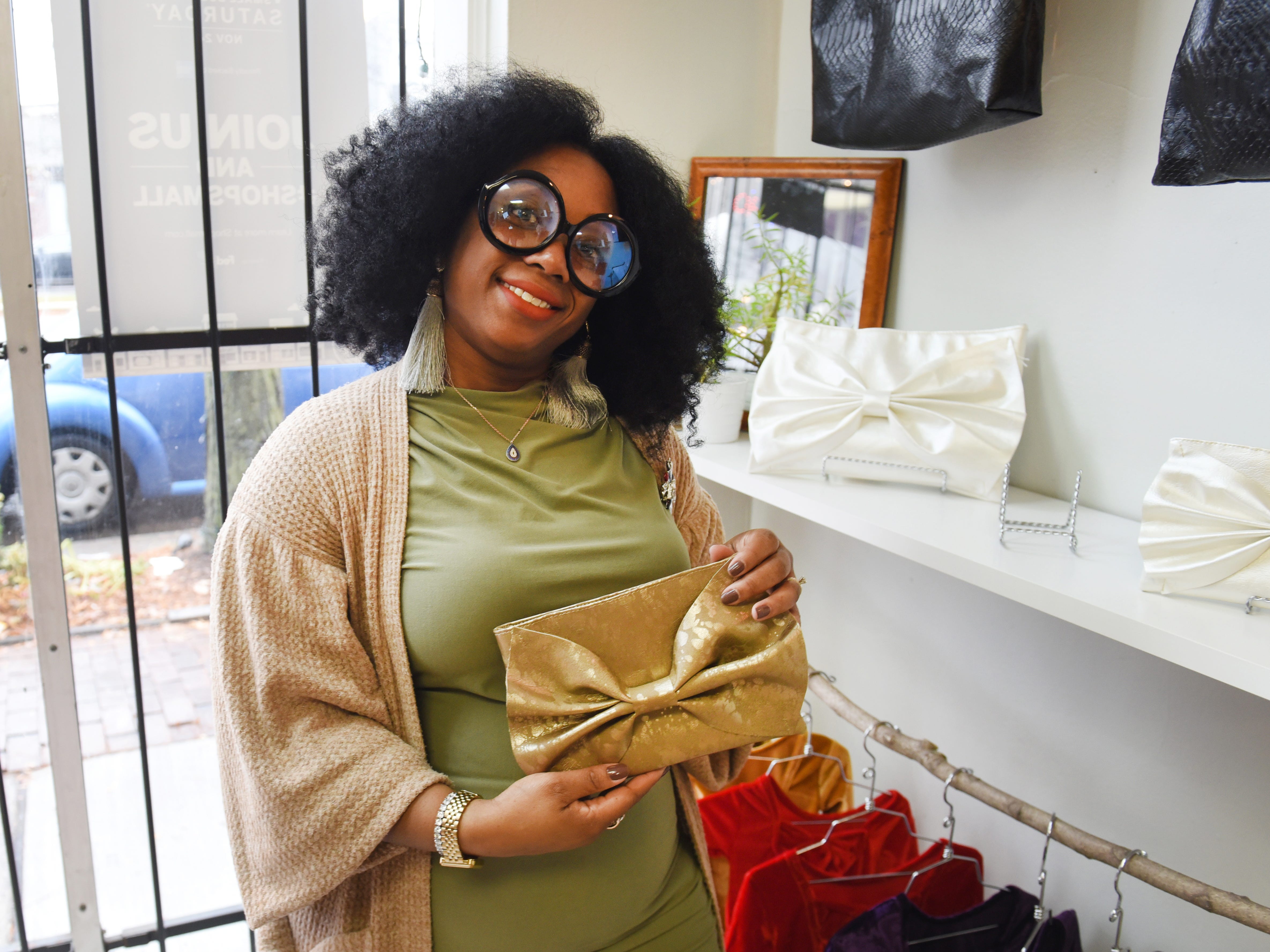 Amira Williams Estell, owner, Mira Estell, show off her custom handbags at a pop-up store along the Avenue of Fashion for Small Business Saturday.