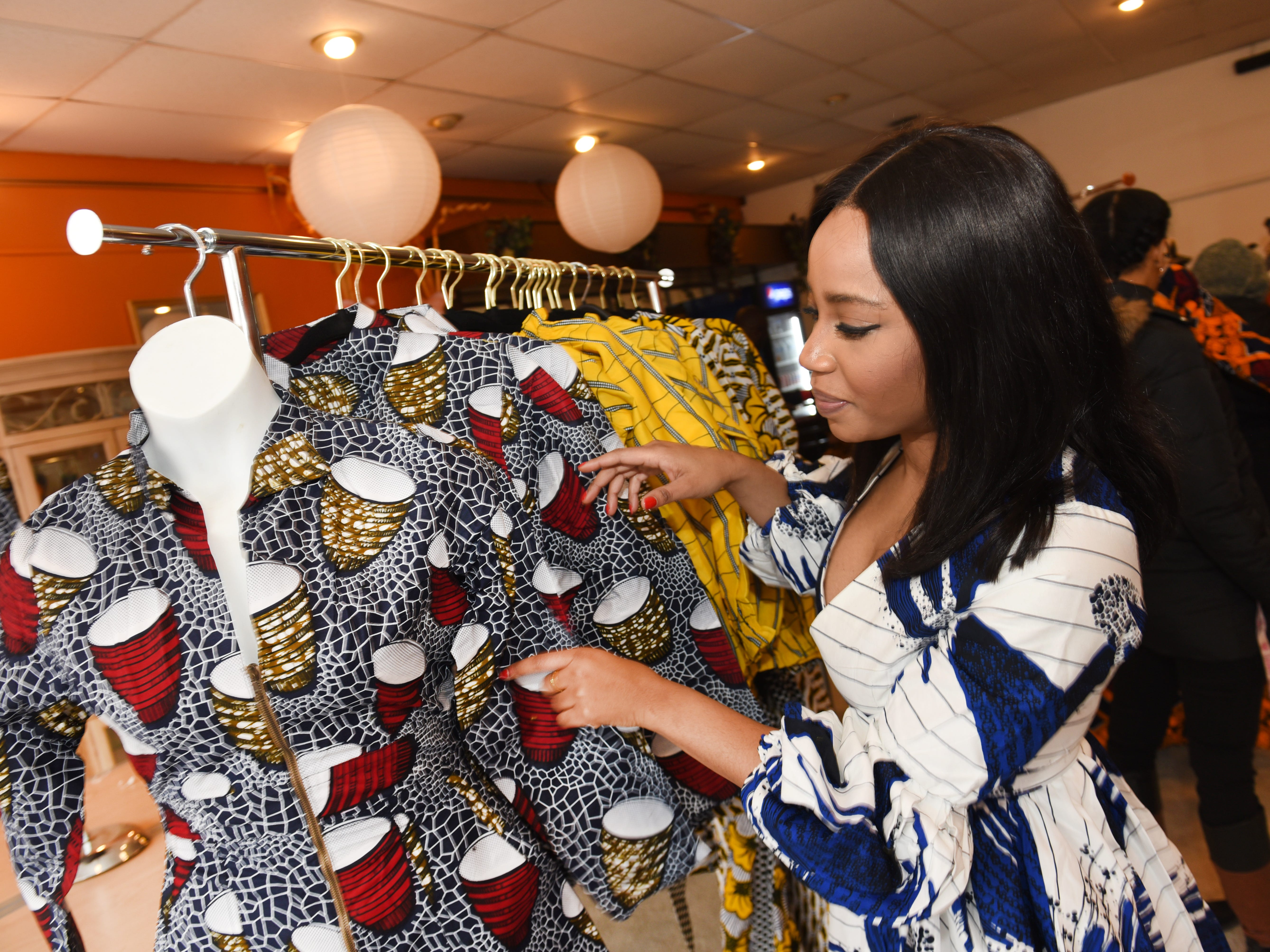 Matilda Harry, owner,  MohoStyle, prepares a clients dress at a  pop-up store along the Avenue of Fashion in Detroit.