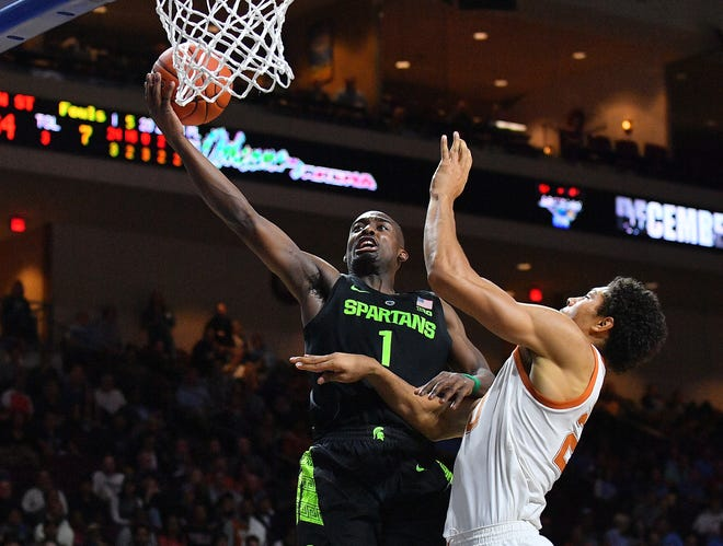 Joshua Langford of the Michigan State Spartans shoots against Jericho Sims of the Texas Longhorns.