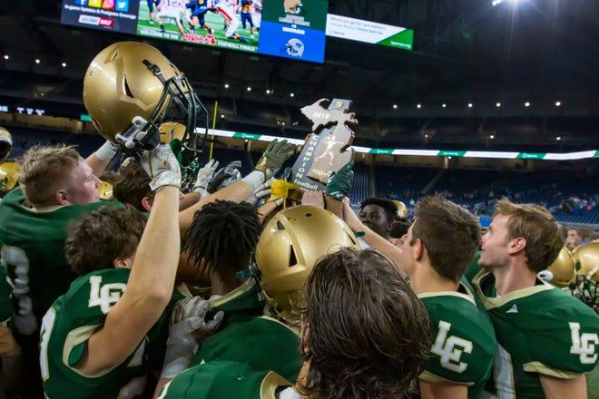 The Jackson Lumen Christi players hoist their third straight state championship Trophy.