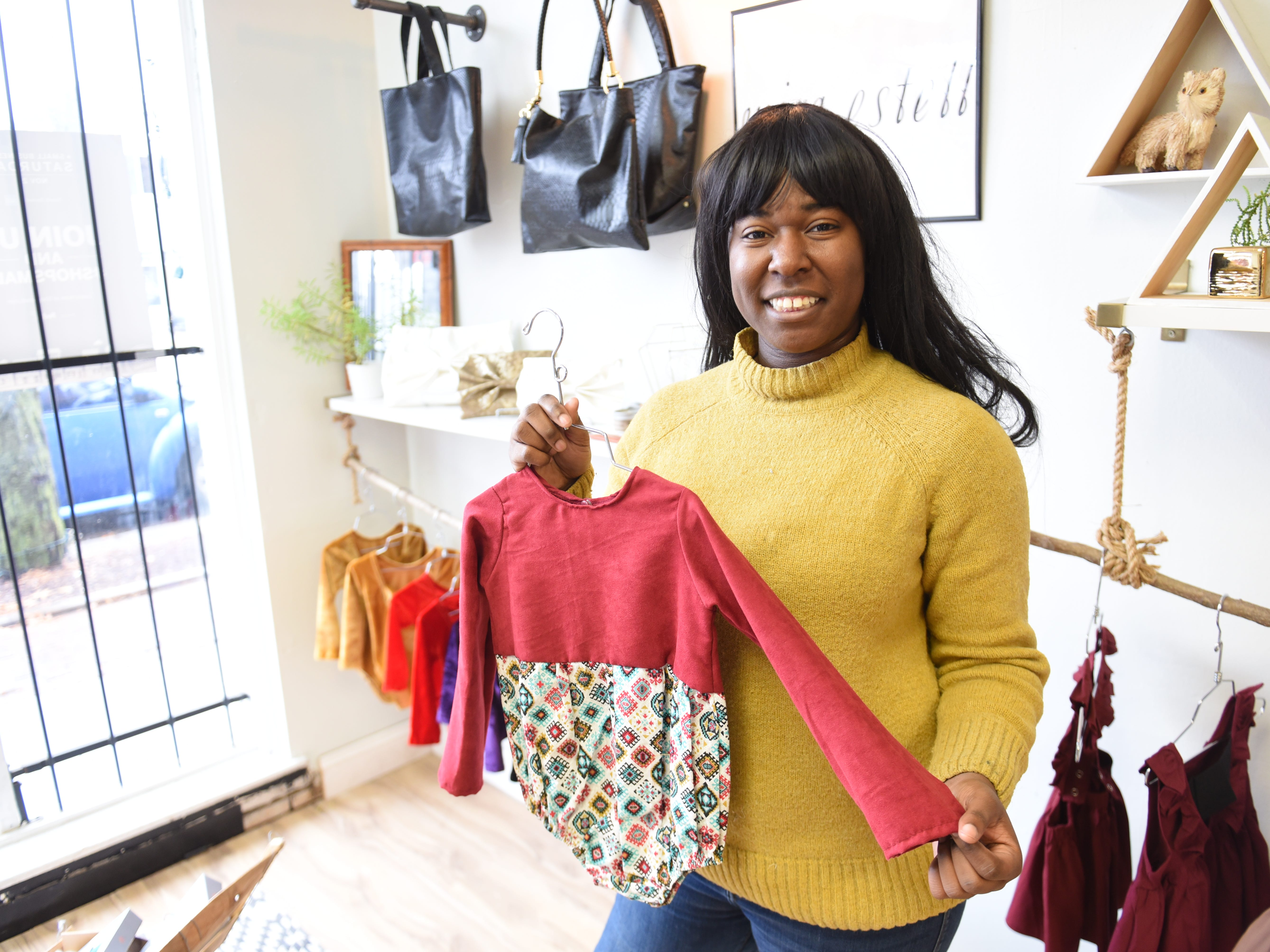 Brianna Williams, owner, DCreated Boutique, shows her hand-made children dress during Small Business Saturday in Detroit.