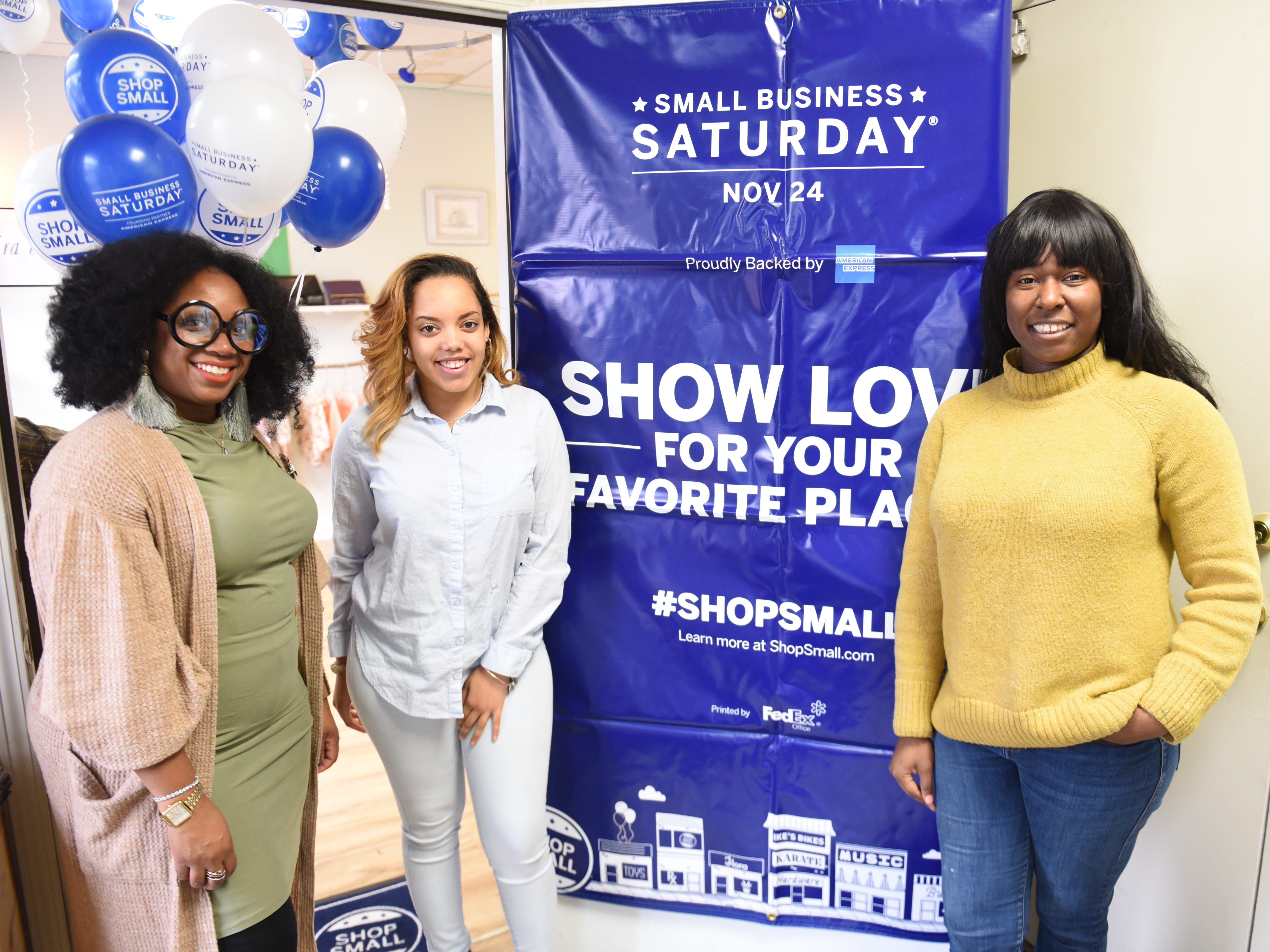 Amira Williams Estell (from left) LaMara Hand and Brianna Williams, owner, Dcreated Boutique, hang a banner promoting Small Business Saturday along the Avenue of Fashion.