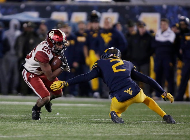 Oklahoma running back Kennedy Brooks (26) tries to get away from West Virginia safety Kenny Robinson Jr. (2) during the second half.